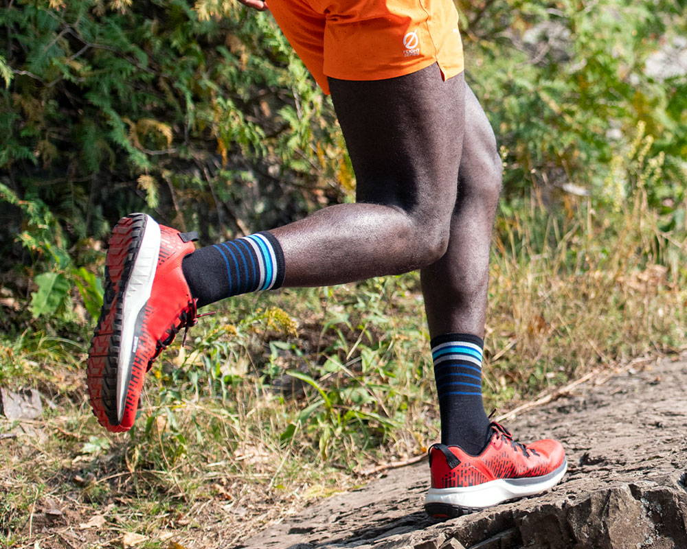 A trail runner wearing darn tough micro crew socks for runners mid stride out in the woods