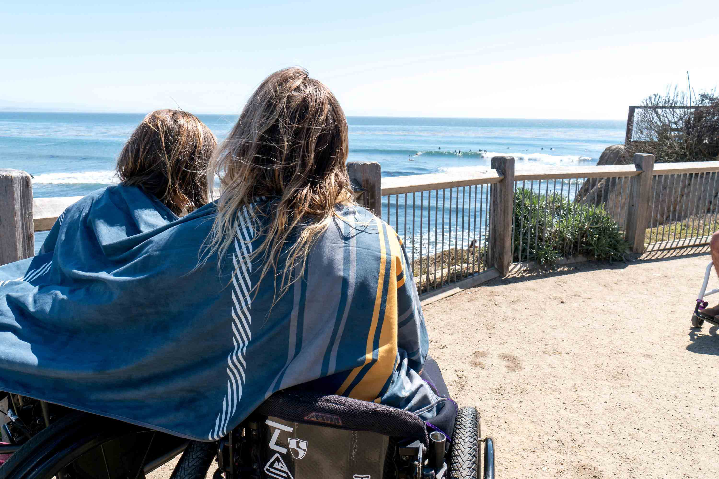 A man and women sitting in wheel chairs with High Fives Shammy wrapped around them watching surfers