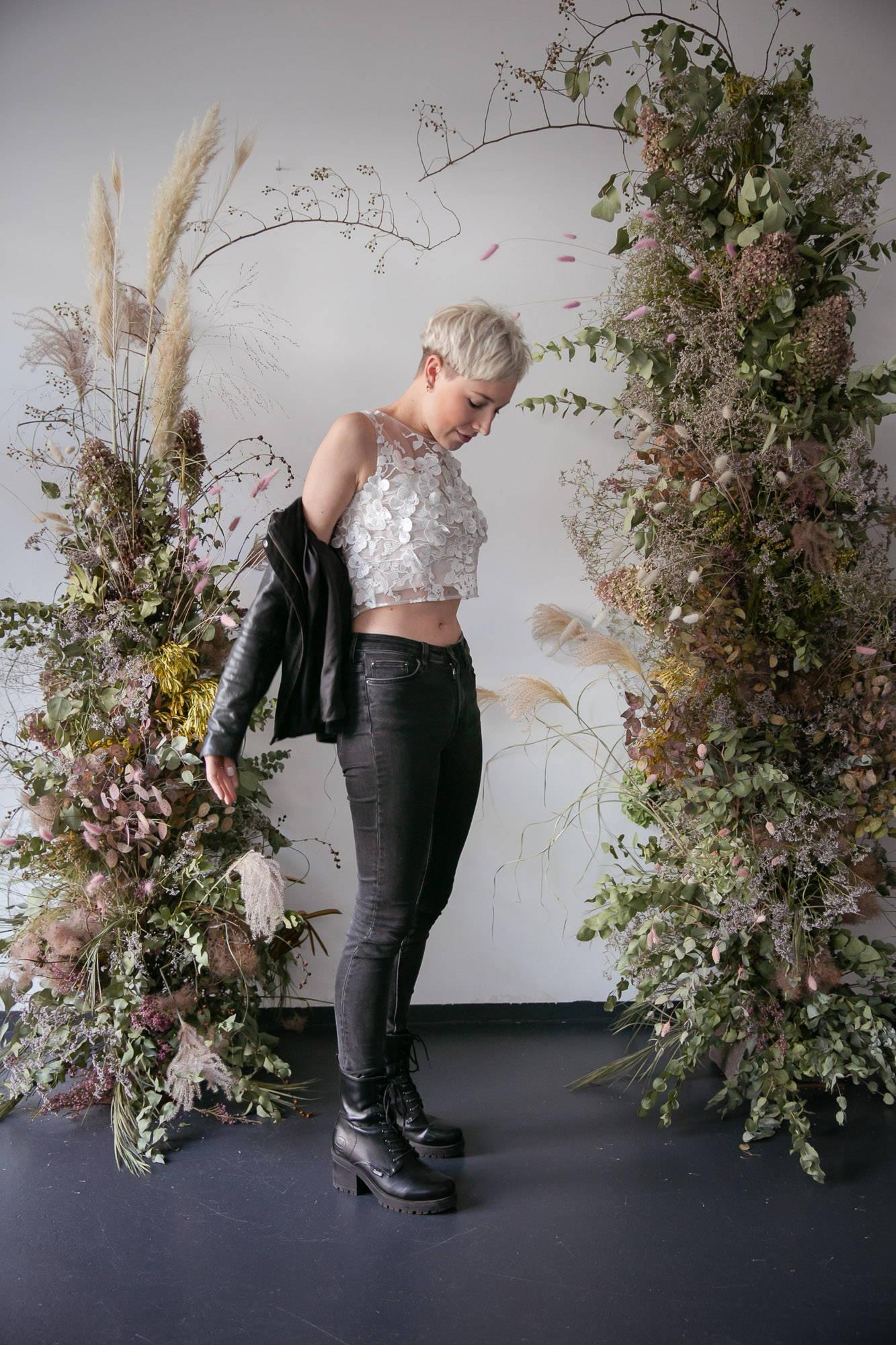 noni Brautmode, ärmelloses Brauttop Luna mit 3D-Blüten, kmbiniert mit Lederjacke und schwarzer Jeans