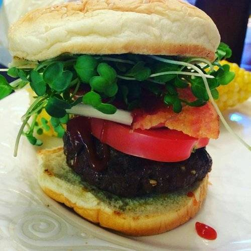 Hamburger with daikon radish microgreens, tomatoes, and ketchup.