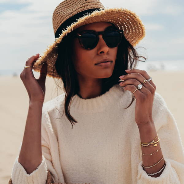 Model sitting on beach in beach hat and sweater wearing Ring Concierge fine jewelry