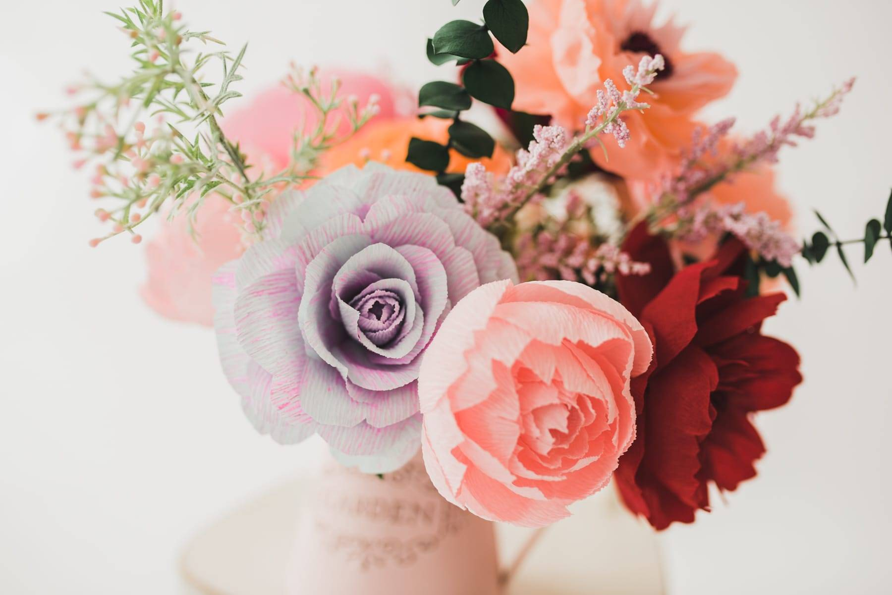 Colorful bouquet of paper flowers, preserved eucalyptus, and faux greenery in a vase on a chair