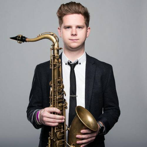 Saxophone player Alex Hahn holding a tenor sax
