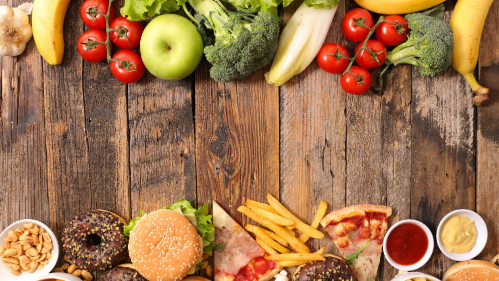healthy food and junk food on a wooden table|why we are in a health crisis
