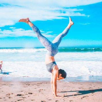 Woman Doing Handstand On A Beach