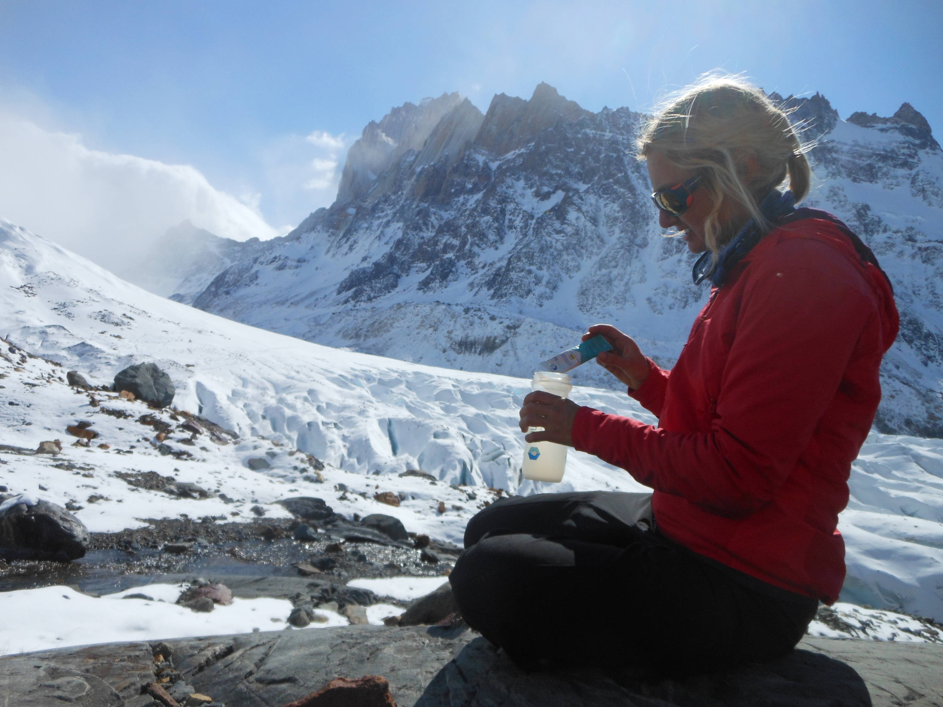 alpine athlete pours Liquid IV into her water bottle.