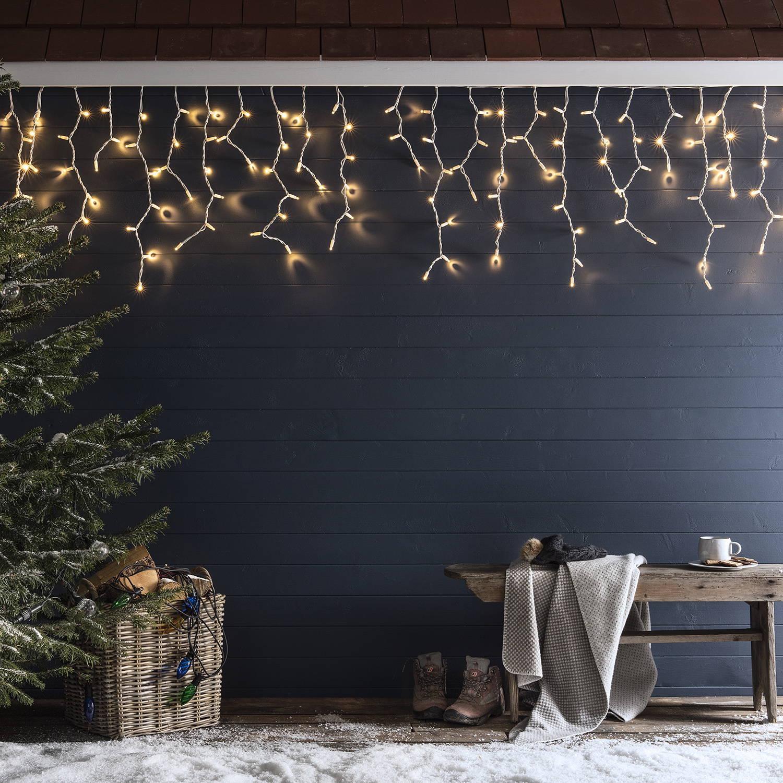 Warmweiße Eiszapfen Lichterkette an Häuserfassade im Schnee.