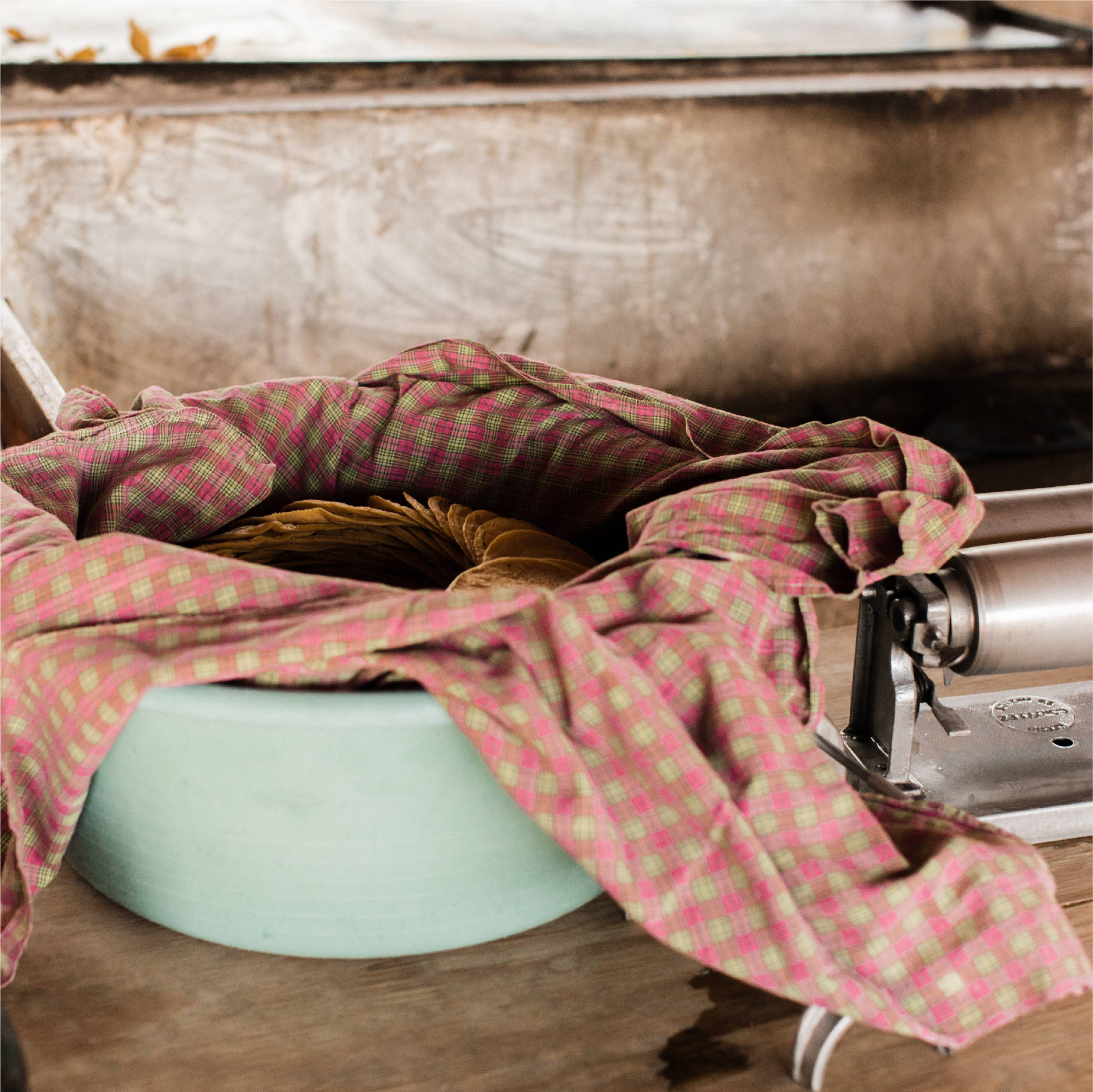 A large stack of tortillas sit wrapped in a large container next to a tortilla press in Honduras.