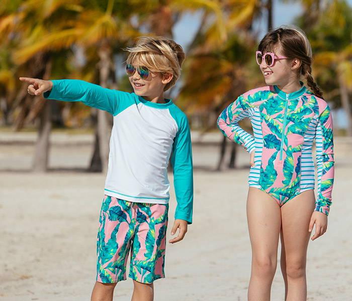 Boy in Preppy Palm Swim Shorts and Rashguard Set and girl in Preppy Palm Unisuit on beach