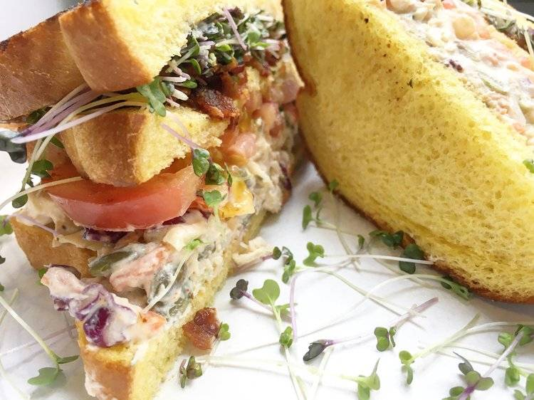 A sandwich of bacon, coleslaw, tomatoes, and salad microgreens.