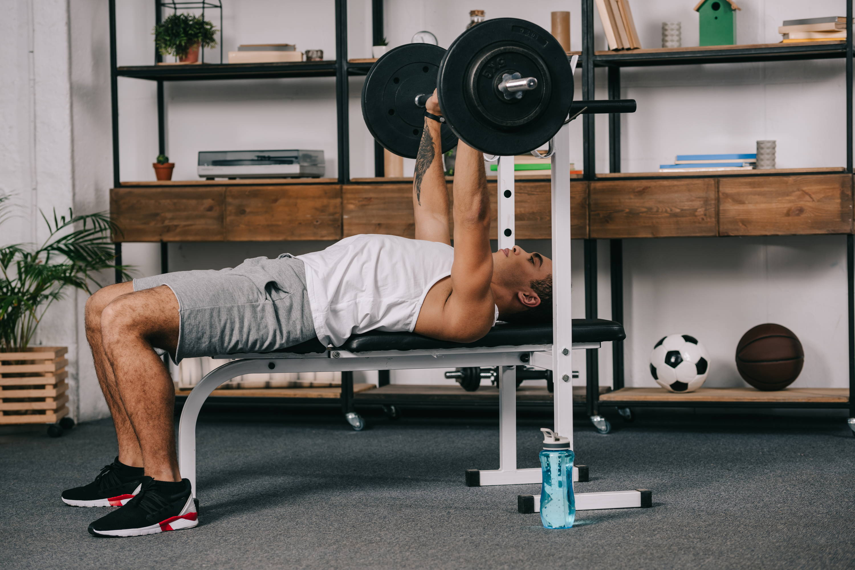 A man working out in his living room on a bench press