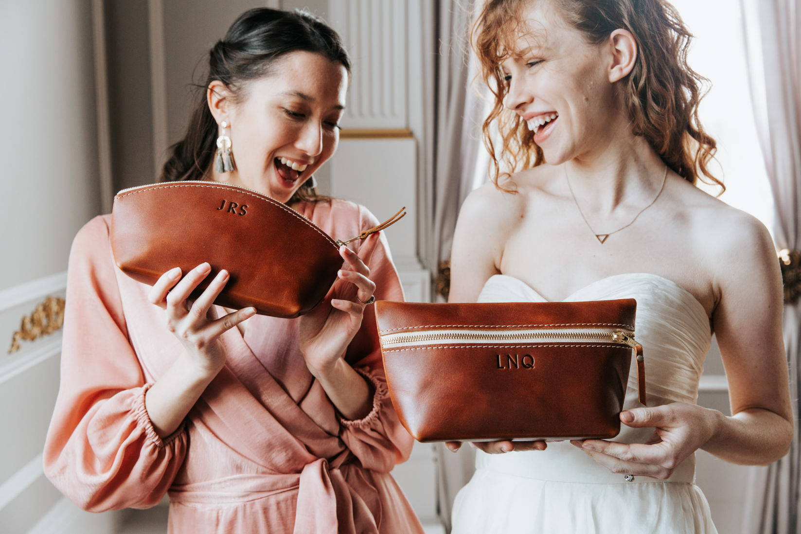 bridesmaid and bride holding makeup bags and smiling