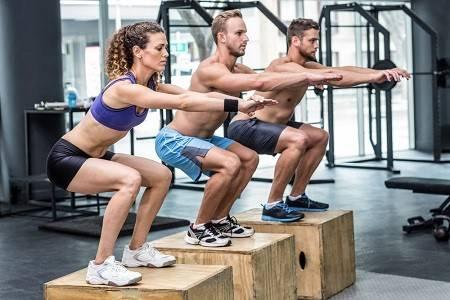 Gruppe trainiert Squats auf Blöcken