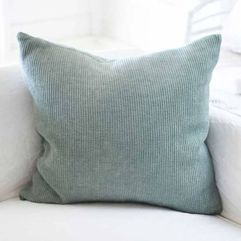 Green Velvet Ribbed Cushion on white sofa