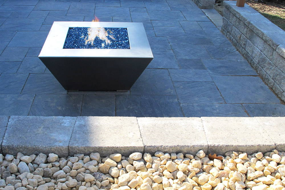 A stainless steel fire pit sits in a stone backyard setting.