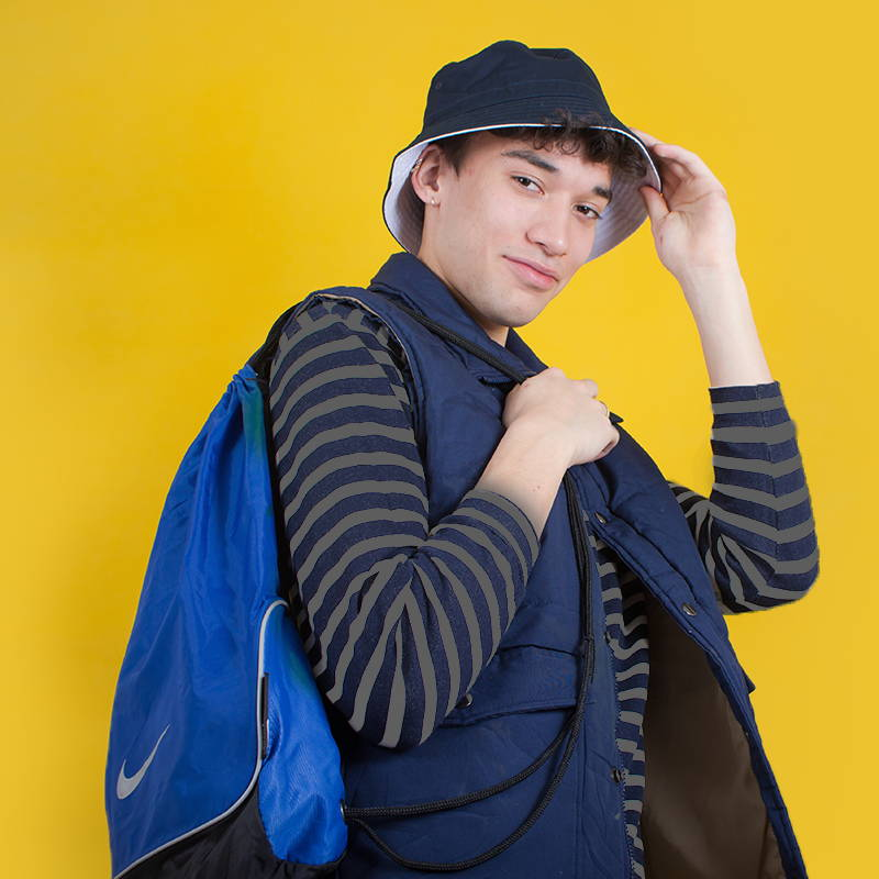 boy in all blue vintage outfit stood against a yellow background