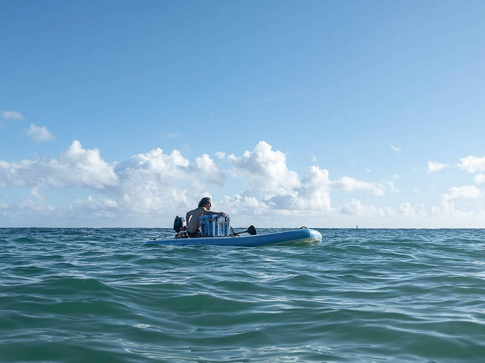 the pau hana bimini board with motor on the sea