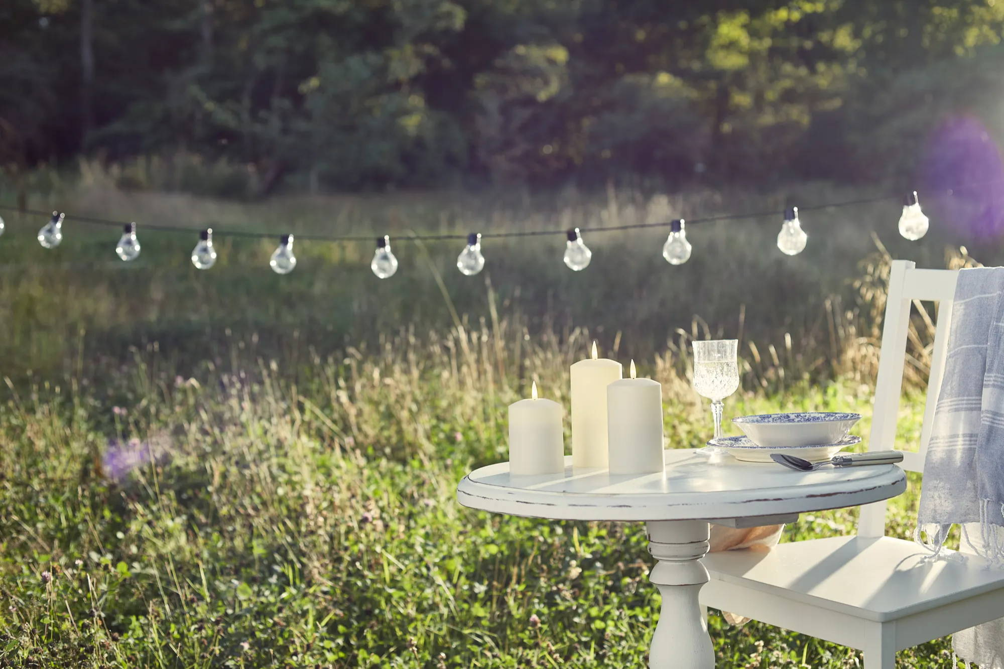 Globe bulb string lights illuminated over alfresco table with flameless candles displayed