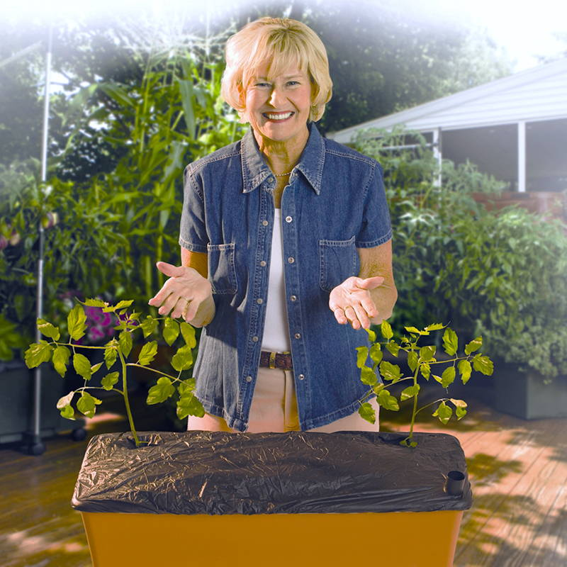 Woman showing off a correctly installed EarthBox black mulch cover with 2 holes cut for her plants