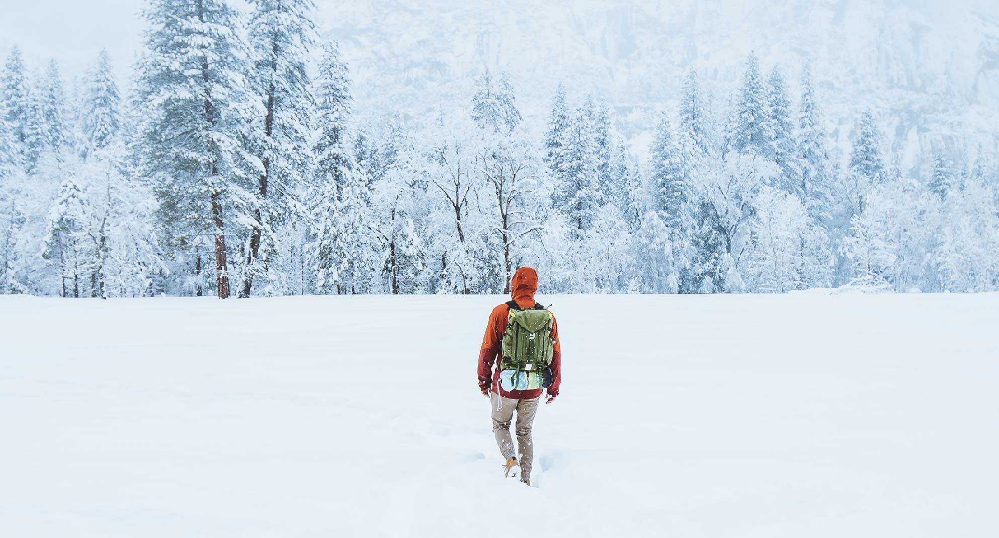 man walking through thick snow with backpack and original puffy blanket yosemite design