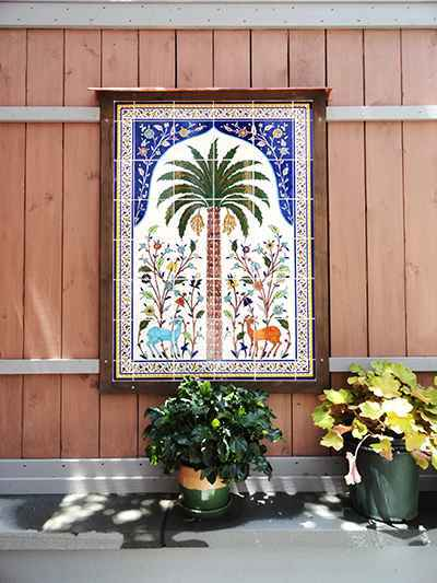 The palm tree tile mural installed in garden