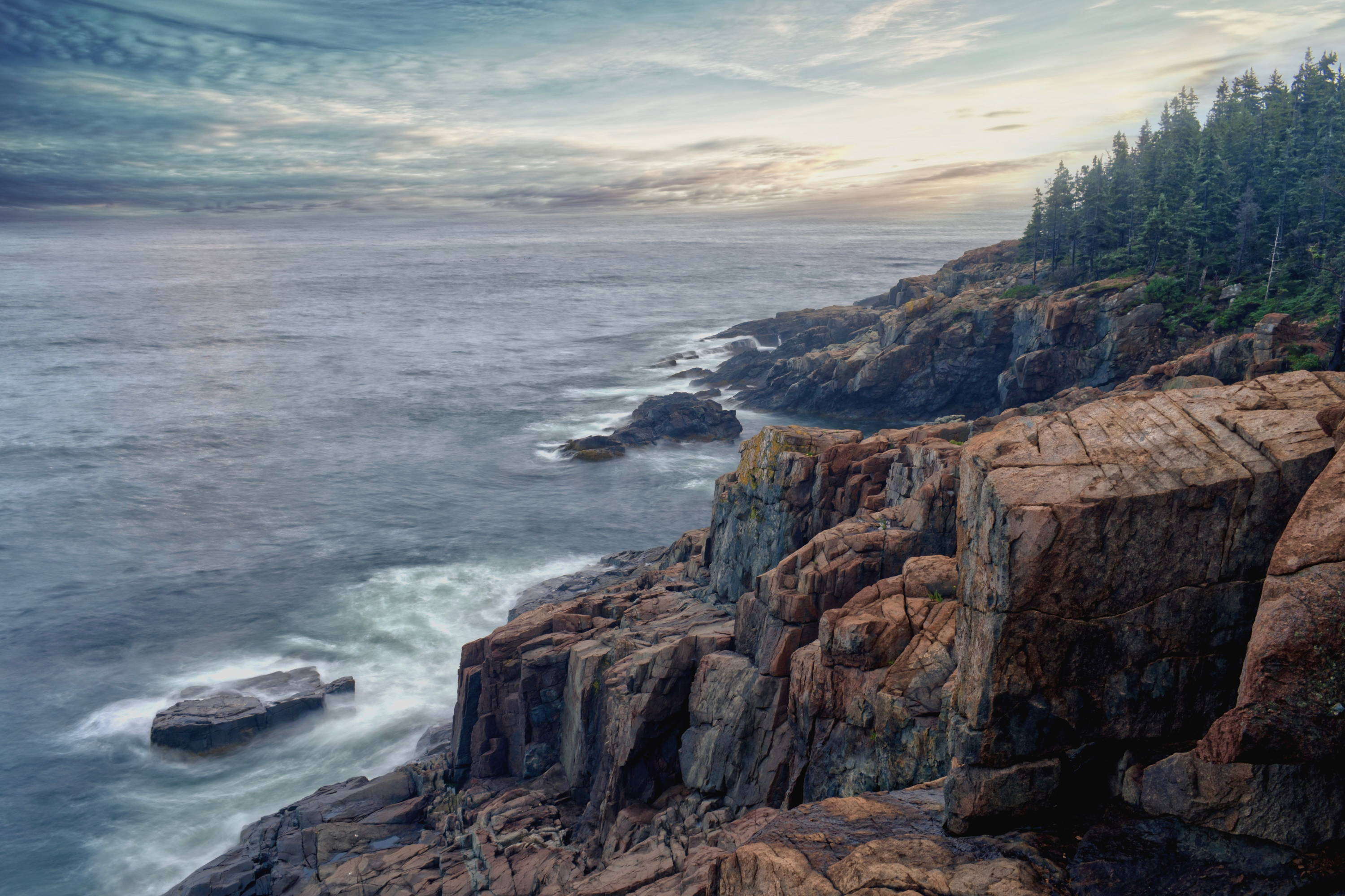 Things to Do in Maine: Acadia National Park Camping & Other Activities. Jagged rocks leading into the ocean with pine trees in background.