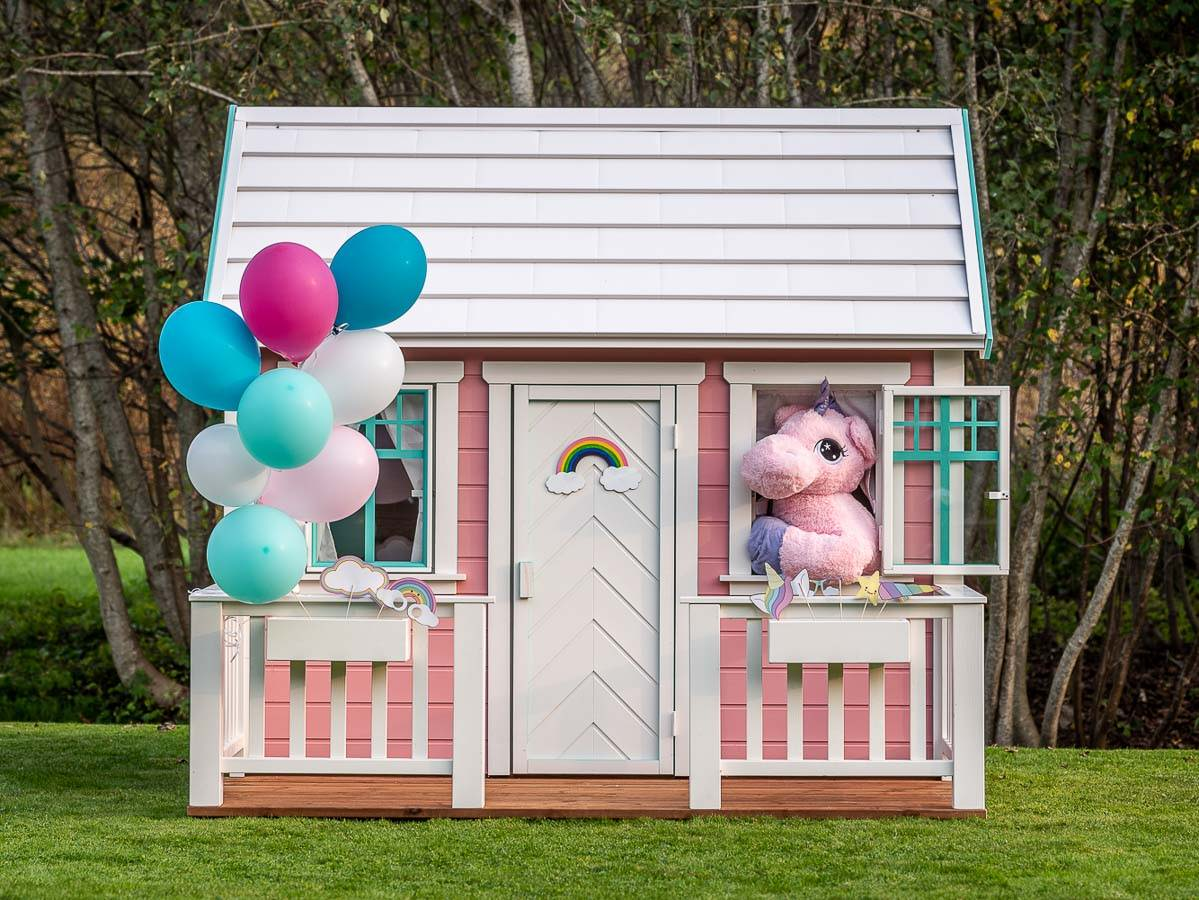 Wooden playhouse in pink color with balloon and a unicorn looking out with a green forest on the background by WholeWoodPlayhouses