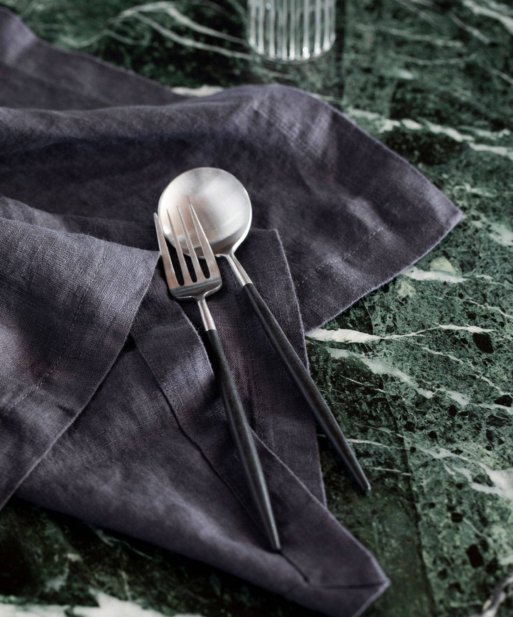 A fork and spoon from the Piper cutlery set by Stanley Rogers resting on the Linen Table Napkin in Slate.