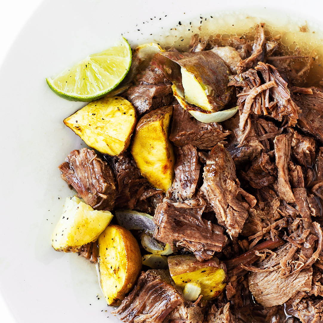 limes, lemons, chuck roast, and potatoes in a bowl