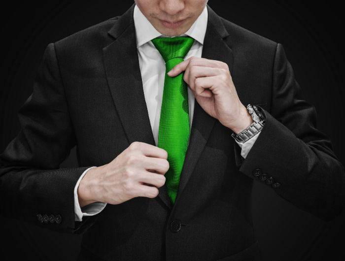 Man adjusting a green necktie