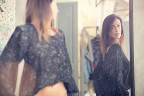 Frau schaut im Spiegel, wie erfolgreich das Abnehmen mit einer Formula-Diät war