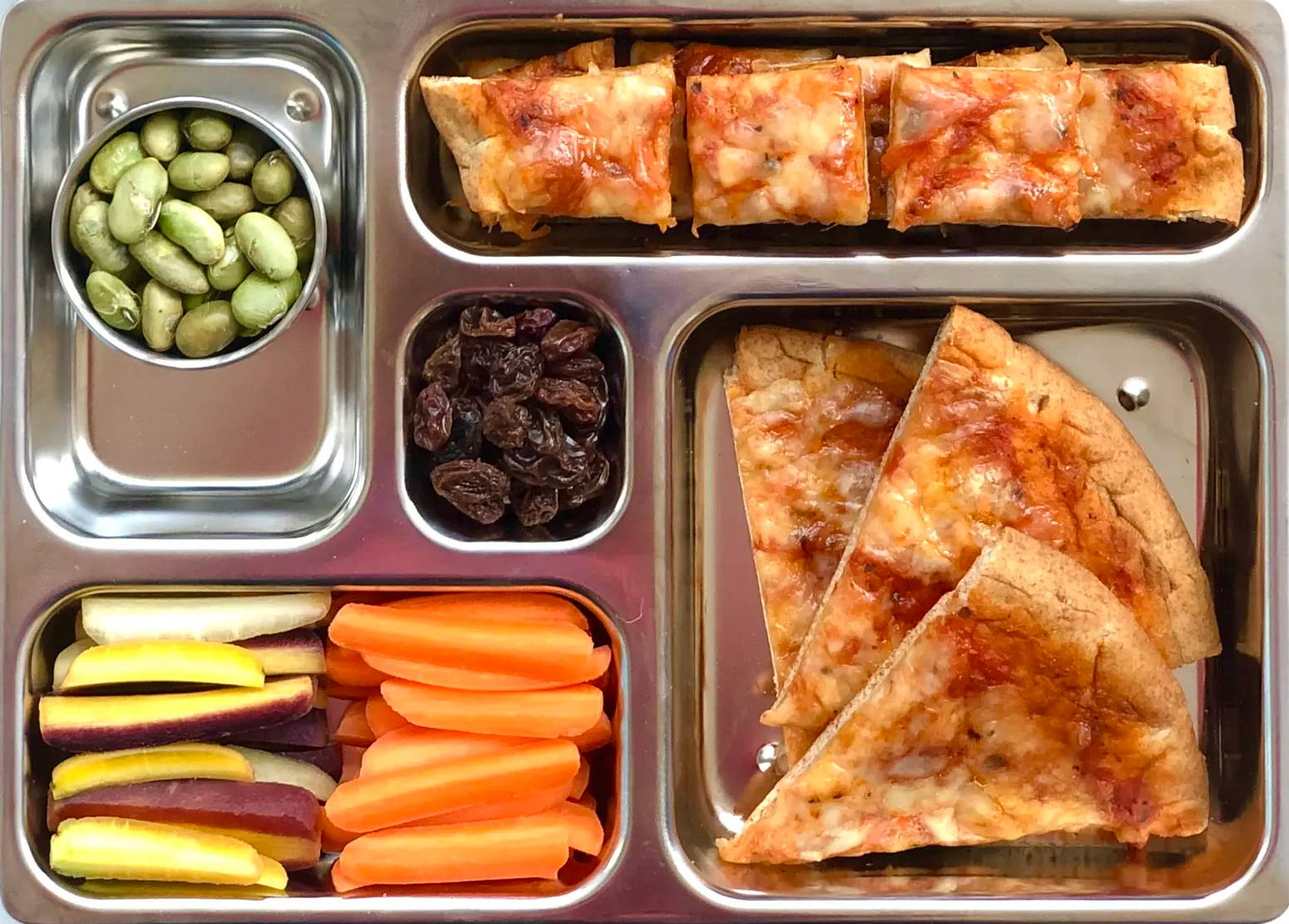 Sneak peek of a kid's quick and healthy school lunch containing Pita Pizza, Sliced Carrots, Dry Roasted Edamame, and Raisins.