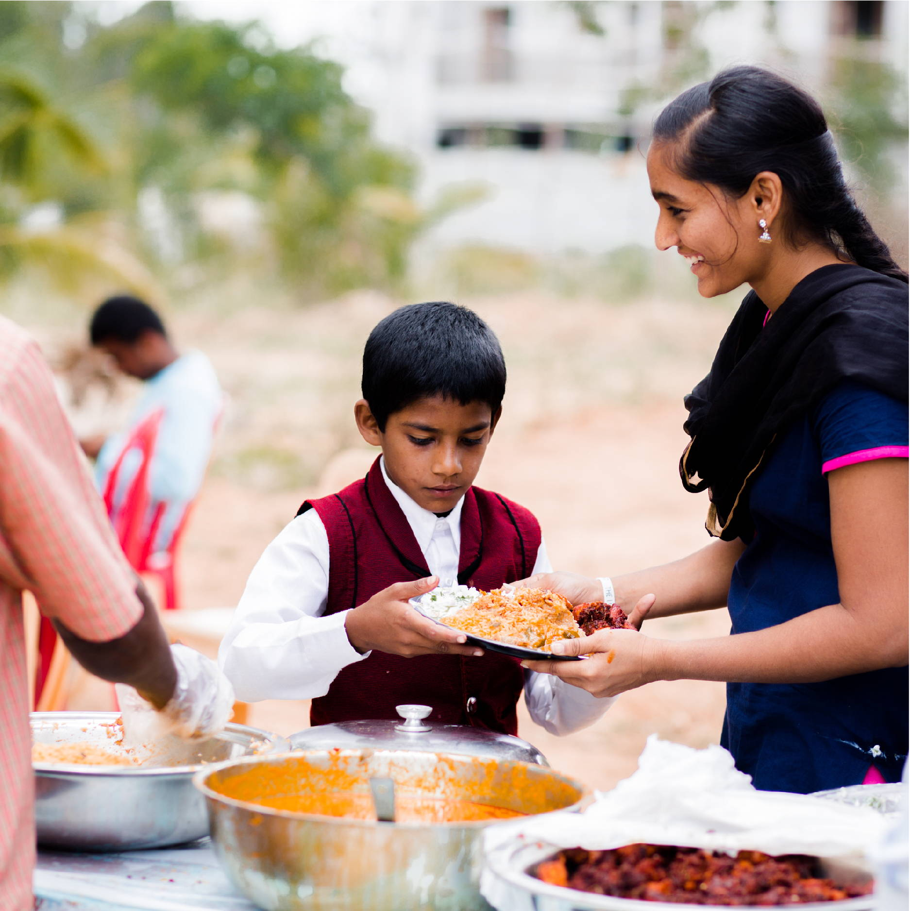 A young boy in red is served a plate of Indian food by a smiling teenage girl at Violet's Children's Home.