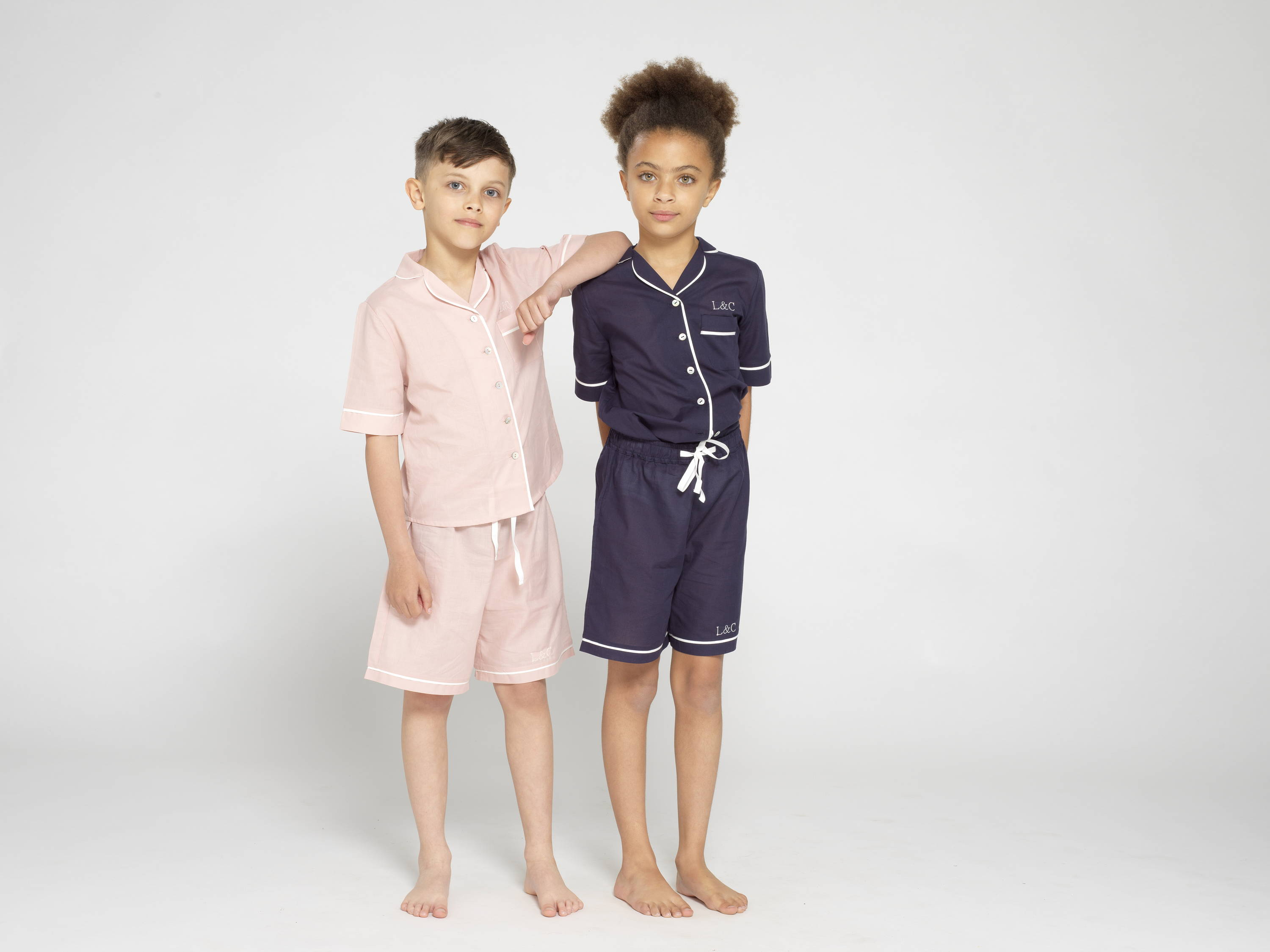 Kids wearing cloud white and midnight blue children pyjamas respectively